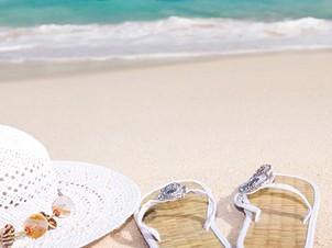 chapeau et tongs sur plage face à l'océan bleu